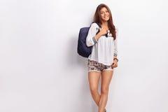 Colegiala adolescente que presenta con una mochila azul Foto de archivo libre de regalías