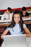 Colegiala adolescente que se sienta con el ordenador portátil en el escritorio Imágenes de archivo libres de regalías