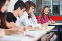 Colegiala adolescente que se sienta en el escritorio Imagen de archivo