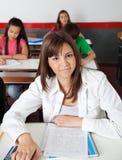 Colegiala adolescente que se sienta en el escritorio en sala de clase Fotografía de archivo