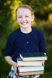 Colegiala adolescente que sostiene la pila de libros y de sonrisa Imagenes de archivo