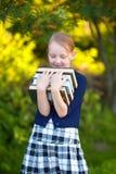 Colegiala adolescente que sostiene la pila de libros y de sonrisa Fotos de archivo libres de regalías