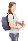 Colegiala adolescente que sostiene una pila de libros Fotografía de archivo