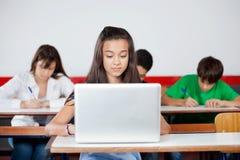 Colegiala adolescente que usa el ordenador portátil en el escritorio Fotos de archivo