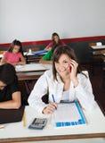 Colegiala adolescente que usa el teléfono móvil mientras que escribe Imagen de archivo libre de regalías