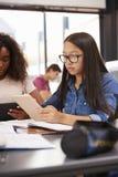 Colegiala adolescente que usa la tableta en la lección Fotografía de archivo