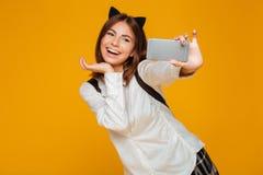 Colegiala adolescente sonriente en uniforme con la presentación de la mochila Fotografía de archivo