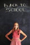 Colegiala adolescente sonriente que se opone con las manos en caderas a b Imagenes de archivo