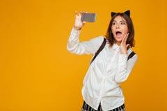 Colegiala adolescente sorprendida en uniforme con la mochila Fotos de archivo