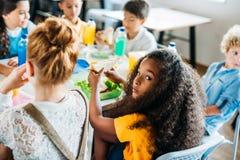 colegiala afroamericana que toma el almuerzo en la cafetería de la escuela con sus compañeros de clase y mirada fotografía de archivo libre de regalías