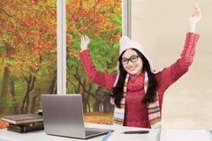 Colegiala alegre con el suéter y el ordenador portátil Foto de archivo