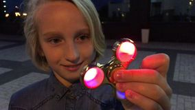 Colegiala alegre que juega con un hilandero luminoso de la persona agitada, igualando al aire libre Un juguete de moda popular almacen de metraje de vídeo