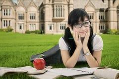 Colegiala asiática atractiva que miente en el parque Imagen de archivo