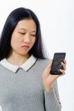 Colegiala asiática con el teléfono móvil agrietado Imágenes de archivo libres de regalías