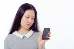 Colegiala asiática con el teléfono móvil agrietado Fotografía de archivo libre de regalías