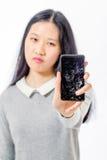 Colegiala asiática con el teléfono móvil agrietado Fotos de archivo libres de regalías