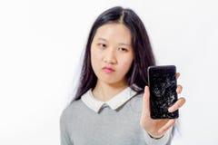 Colegiala asiática con el teléfono móvil agrietado Foto de archivo