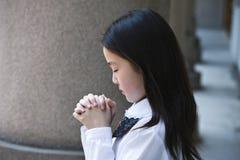 Colegiala asiática que ruega Foto de archivo