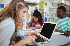 Colegiala atenta que usa el ordenador portátil con sus compañeros de clase en estudiar el fondo Foto de archivo