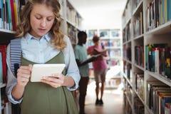 Colegiala atenta que usa la tableta digital en biblioteca Imagen de archivo libre de regalías