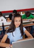 Colegiala bastante adolescente que se sienta con el ordenador portátil adentro Fotografía de archivo libre de regalías