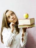 Colegiala bastante rubia de la muchacha con los libros y la manzana Educación Imagen de archivo libre de regalías