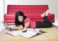Colegiala bonita que estudia en la alfombra en casa Fotografía de archivo