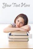 Colegiala bonita que pone en los libros en sala de clase Imágenes de archivo libres de regalías