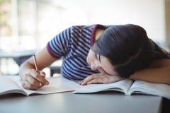 Colegiala cansada que duerme en sala de clase Fotografía de archivo