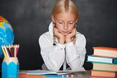 Colegiala cansada que se sienta en el escritorio en sala de clase imágenes de archivo libres de regalías