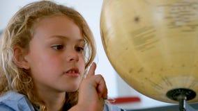 Colegiala caucásica linda que estudia el globo en una sala de clase en la escuela almacen de video