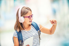 Colegiala con el bolso, mochila Retrato de la colegiala adolescente feliz moderna con los auriculares y la tableta de la mochila  Imagenes de archivo