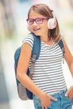 Colegiala con el bolso, mochila Retrato de la colegiala adolescente feliz moderna con los auriculares y la tableta de la mochila  Imagen de archivo
