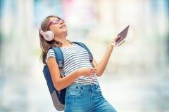 Colegiala con el bolso, mochila Retrato de la colegiala adolescente feliz moderna con los auriculares y la tableta de la mochila  Fotos de archivo