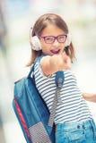 Colegiala con el bolso, mochila Retrato de la colegiala adolescente feliz moderna con los auriculares y la tableta de la mochila  Foto de archivo libre de regalías