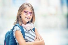 Colegiala con el bolso, mochila Retrato de la colegiala adolescente feliz moderna con los auriculares y la tableta de la mochila  Imágenes de archivo libres de regalías