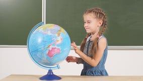 Colegiala con el globo en pizarra de la sala de clase en fondo almacen de video