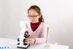 Colegiala con el microscopio moderno Imágenes de archivo libres de regalías