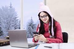 Colegiala con el suéter usando smartphone Fotos de archivo