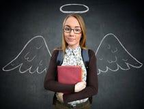 Colegiala con las alas divertidas del ángel Imagen de archivo