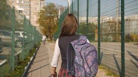 Colegiala con las mochilas en la luz de la puesta del sol que vuelve a casa de la escuela, la visión desde el lado trasero almacen de video