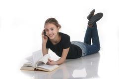 Colegiala con un libro y un teléfono en un fondo blanco Imagen de archivo