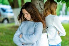Colegiala de dos muchachas En el verano en parque de la ciudad Ofendido en uno a Los conceptos negativos son niños difíciles Imagen de archivo