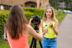 Colegiala de dos muchachas Verano en naturaleza Escribe el vídeo a la cámara En sus manos sostiene una botella de agua y Imagen de archivo libre de regalías