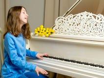 Colegiala de la muchacha cerca del piano en el cual miente un ramo de flor Fotografía de archivo libre de regalías