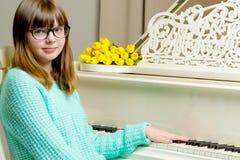 Colegiala de la muchacha cerca del piano en el cual miente un ramo de flor Fotografía de archivo