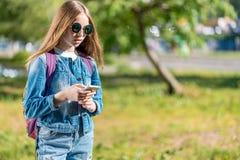 Colegiala de la muchacha detrás de la mochila Vestido en ropa de los vaqueros con las gafas de sol En su mano sostiene un smartph Foto de archivo