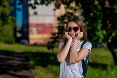 Colegiala de la muchacha En el verano después de la escuela Detrás de la mochila Gafas de sol en la forma del corazón Espacio lib Fotografía de archivo