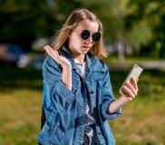 Colegiala de la muchacha en verano en parque después de la escuela En sus manos sostiene un smartphone Gesticula la comunicación  Foto de archivo libre de regalías