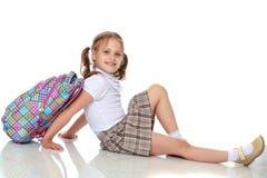 Colegiala de la muchacha que se sienta en el piso Imágenes de archivo libres de regalías